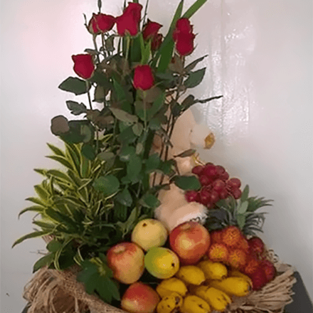 Basket of fruit with six red roses