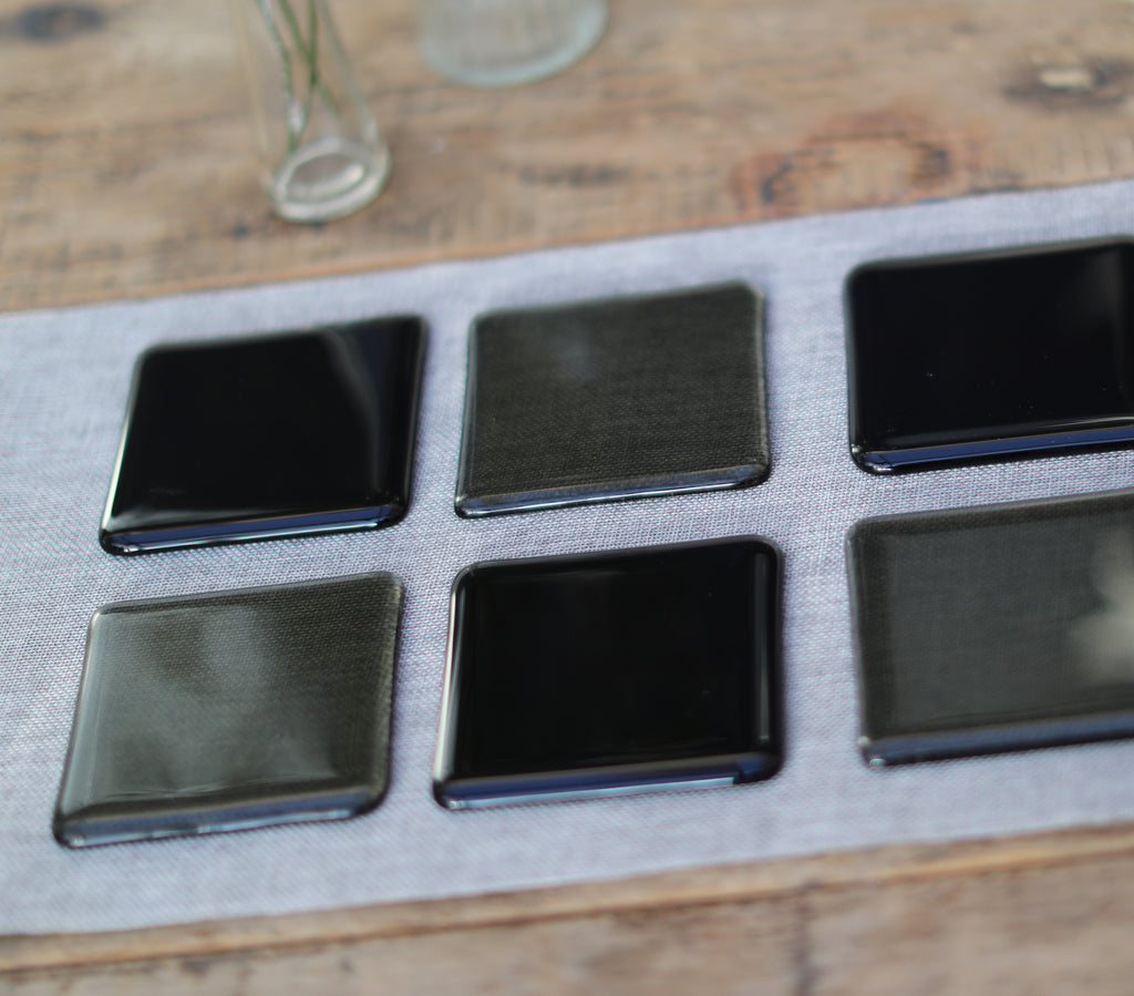 Charcoal grey transparent fused art glass coaster 100x100mm size in use on table