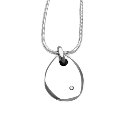 Elegantly simple pebble like flat silver pendant set with a high quality diamond by jeweller Annika Rutlin