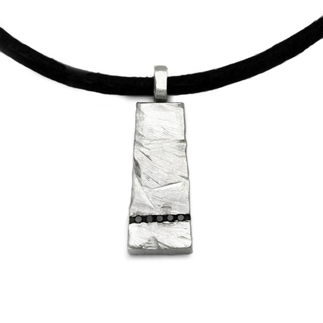 A solid silver rough textured pendant with a line of bleck diamonds by Annika Rutlin