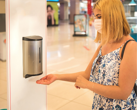 Woman Using Hand Sanitiser In Shopping Mall