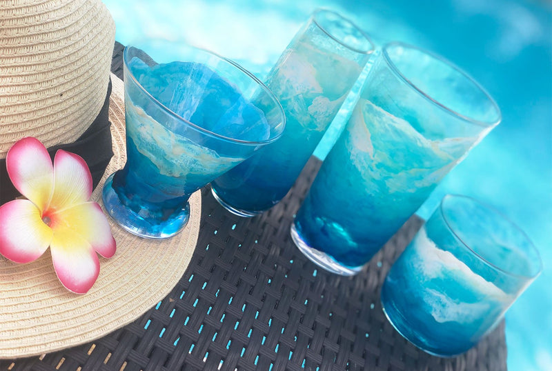 Beautiful set of blue and white hand-painted cocktail glasses with layers of ocean waves washing up a beach, seen from a birds eye view. Sitting with a tropical flower beside a pool.