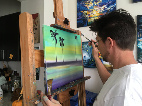 Artist at work painting Tropical Scenes