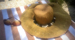 Tropical getaway showing a straw beach hat wrapped with shells and stylish sunglasses lying on a tan striped beach towel
