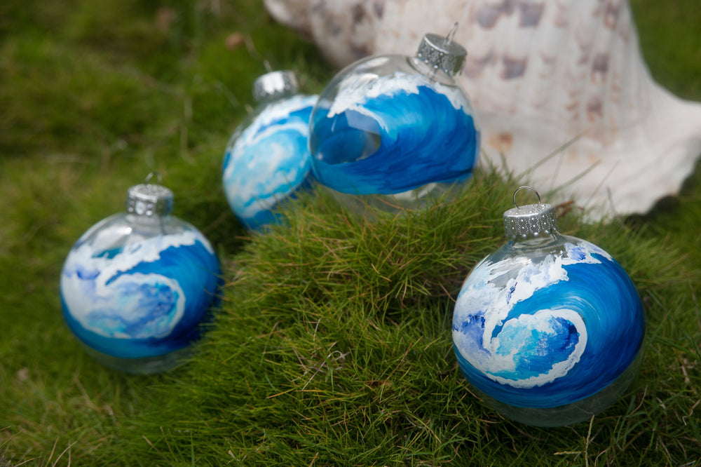 Set of beach themed ornaments with hand-painted blue waves sitting on a bed of bright green moss.