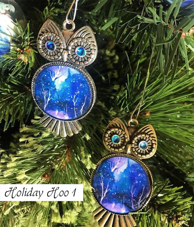 Silver and bronze owl Christmas tree ornaments with blue and white painted chests and swirled eyes.