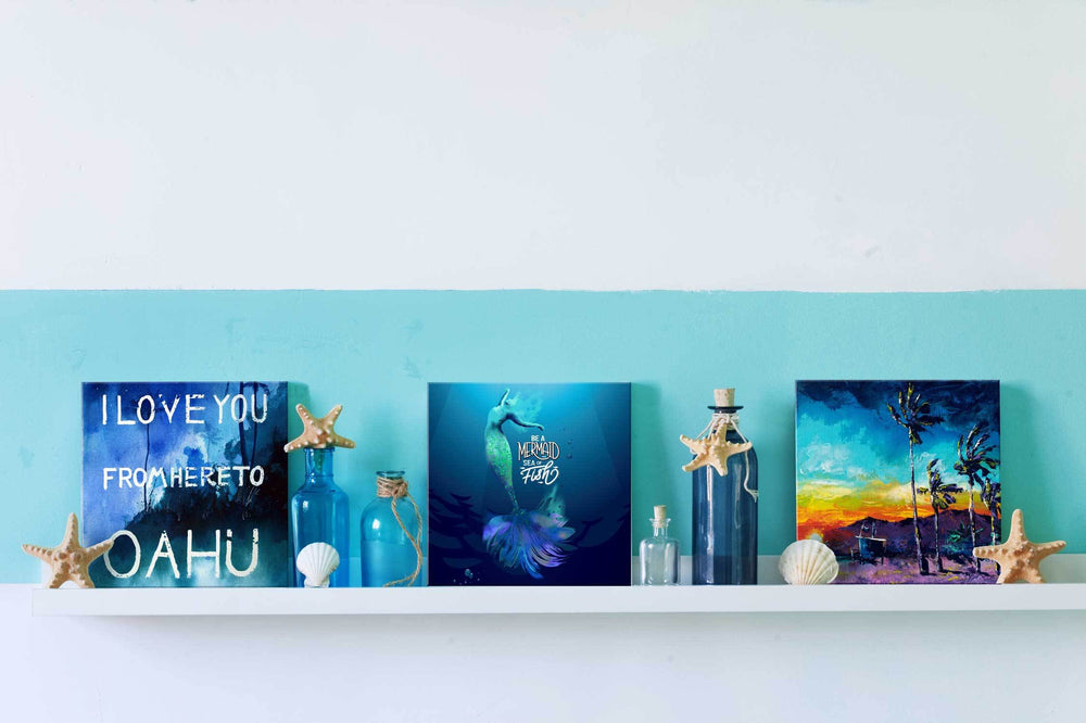 3 beach prints on small shelf with ocean and beach house décor, including Hawaiian, mermaid, and SoCal paintings