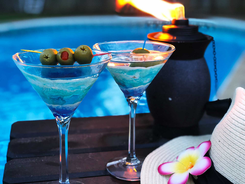 Pair of ocean wave martini glasses, with full cocktails and olive garnishes. Sitting beside a pool with a tropical flower hat and tiki bowl.
