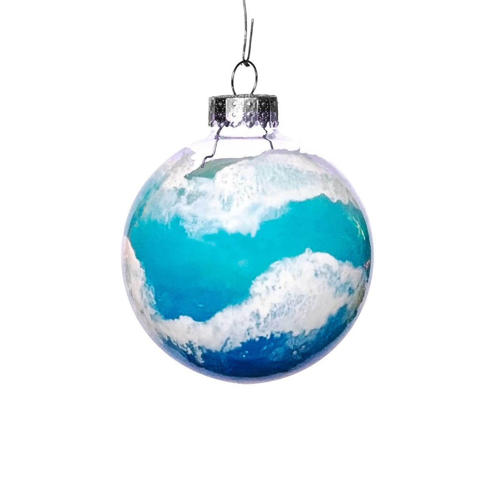 Beach Christmas tree ornaments with layers of beach waves on glass sphere on a blue ornament Christmas tree.