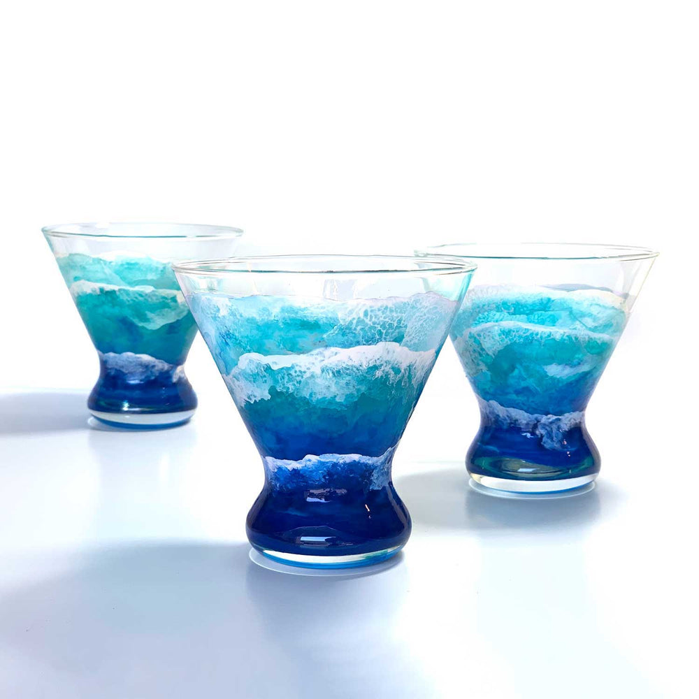 Trio of beautiful blue ocean wave glassware. Hand-painted stemless martini glasses, displayed as best home bar decor by Nelson.