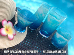 Set of 4 hand-painted glasses with blue and turquoise ocean waves, sitting by a hat with a flower