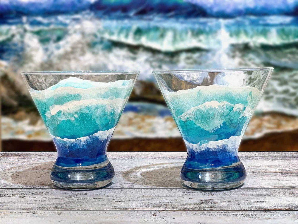 Pair of custom glasses for wedding, with blue ocean waves seen from birds-eye-view, sitting on a wood table in front of a beach oil painting of crashing waves.