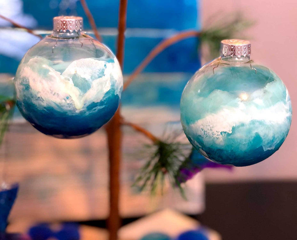 Pair of blue and white Christmas ornaments hanging with other coastal Christmas tree decorations and surfing Santa decor.