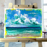 Original painting of sunny beach with turquoise ocean under puffy white clouds on artist's easel