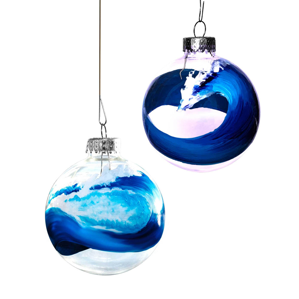 Pair of clear glass ball Christmas ornaments with hand-painted blue ocean wave curling around each ornament by Nelson Ruger.