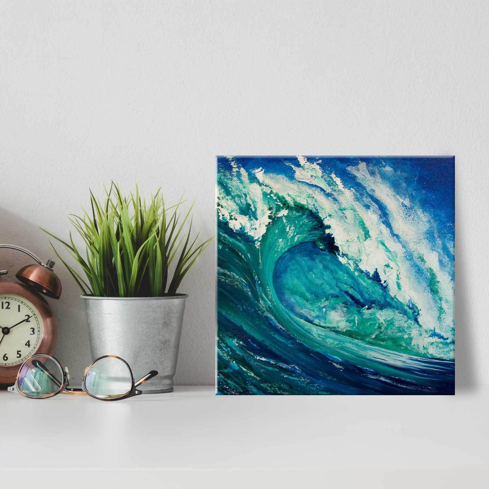 Square printed tile with turquoise painted wave leaning against white wall with minimalist décor