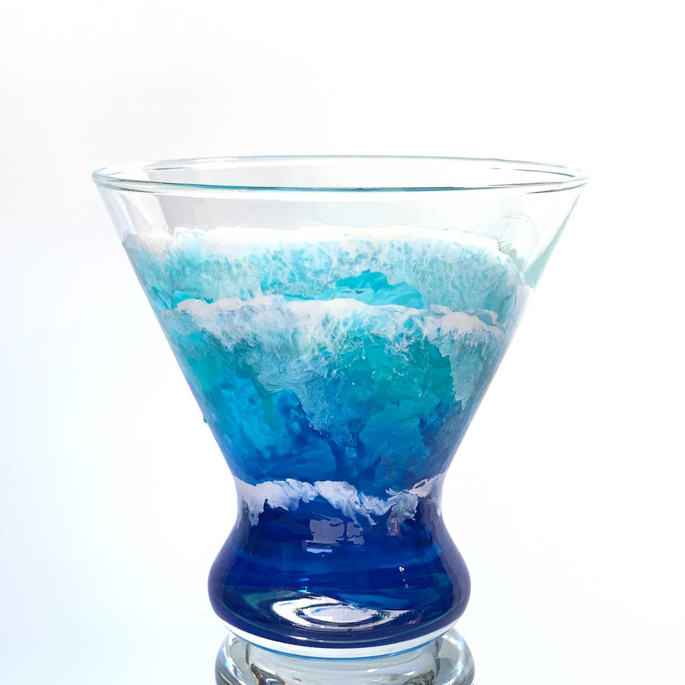Custom cocktail glassware of hand-painted ocean waves washing up a stemless martini glass in blue, white, and turquoise.