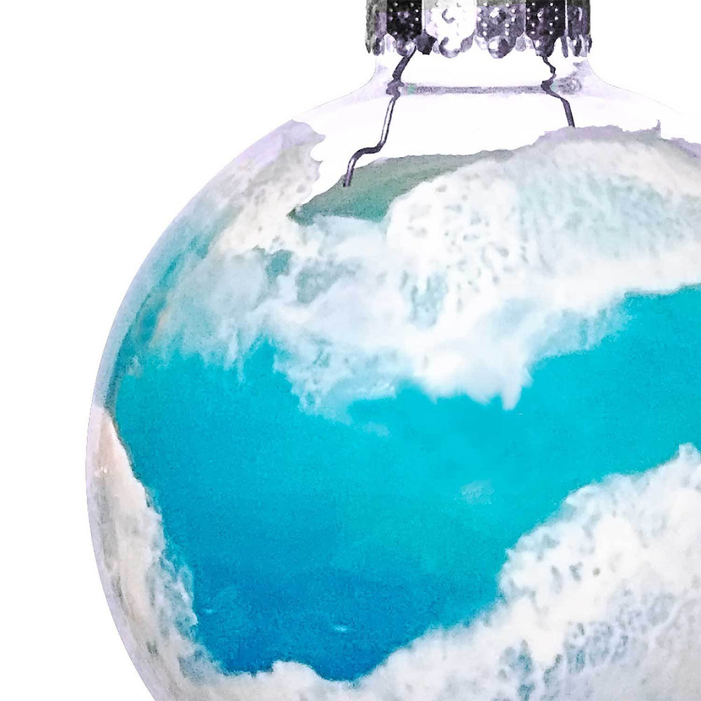 Close view of coastal Christmas tree ornaments with light blue and white rolling ocean waves on a clear glass ball.