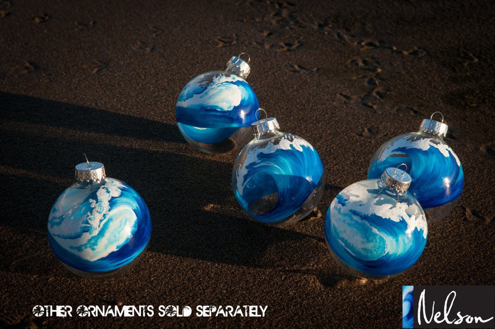 Set of blue and white Christmas ornaments with painted ocean waves, sitting on wet sand at the beach.