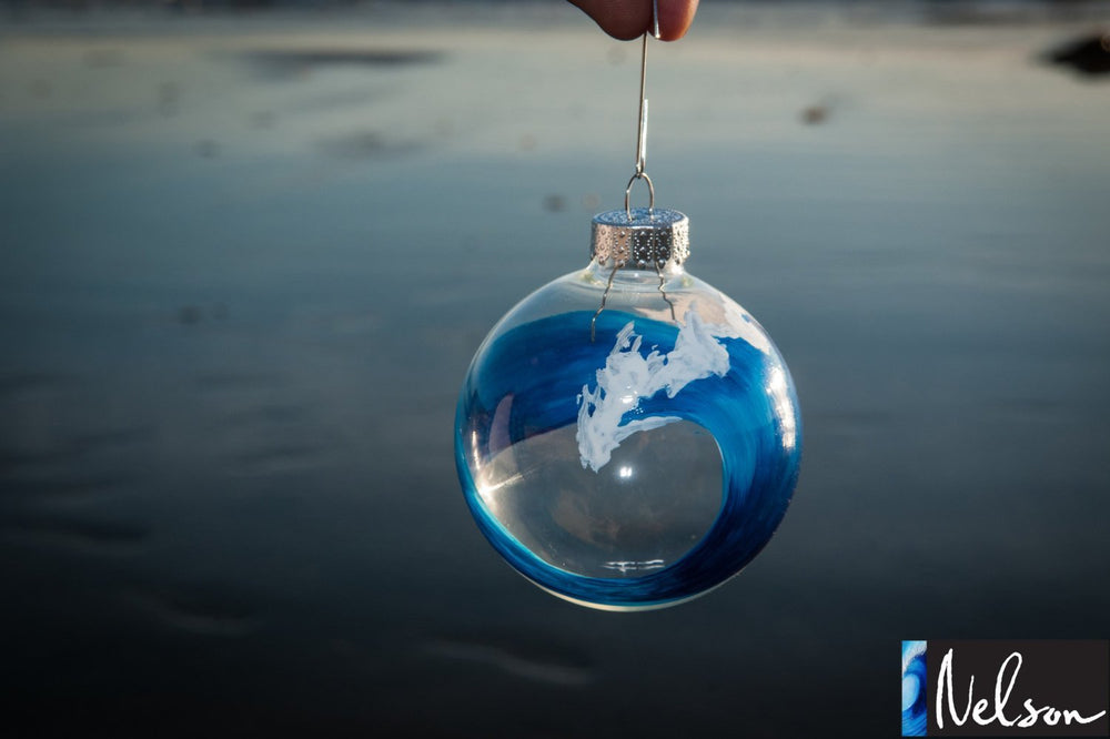 Blue and white Christmas ornament with painted ocean wave on glass ball ornament, being held in front of beach landscape.