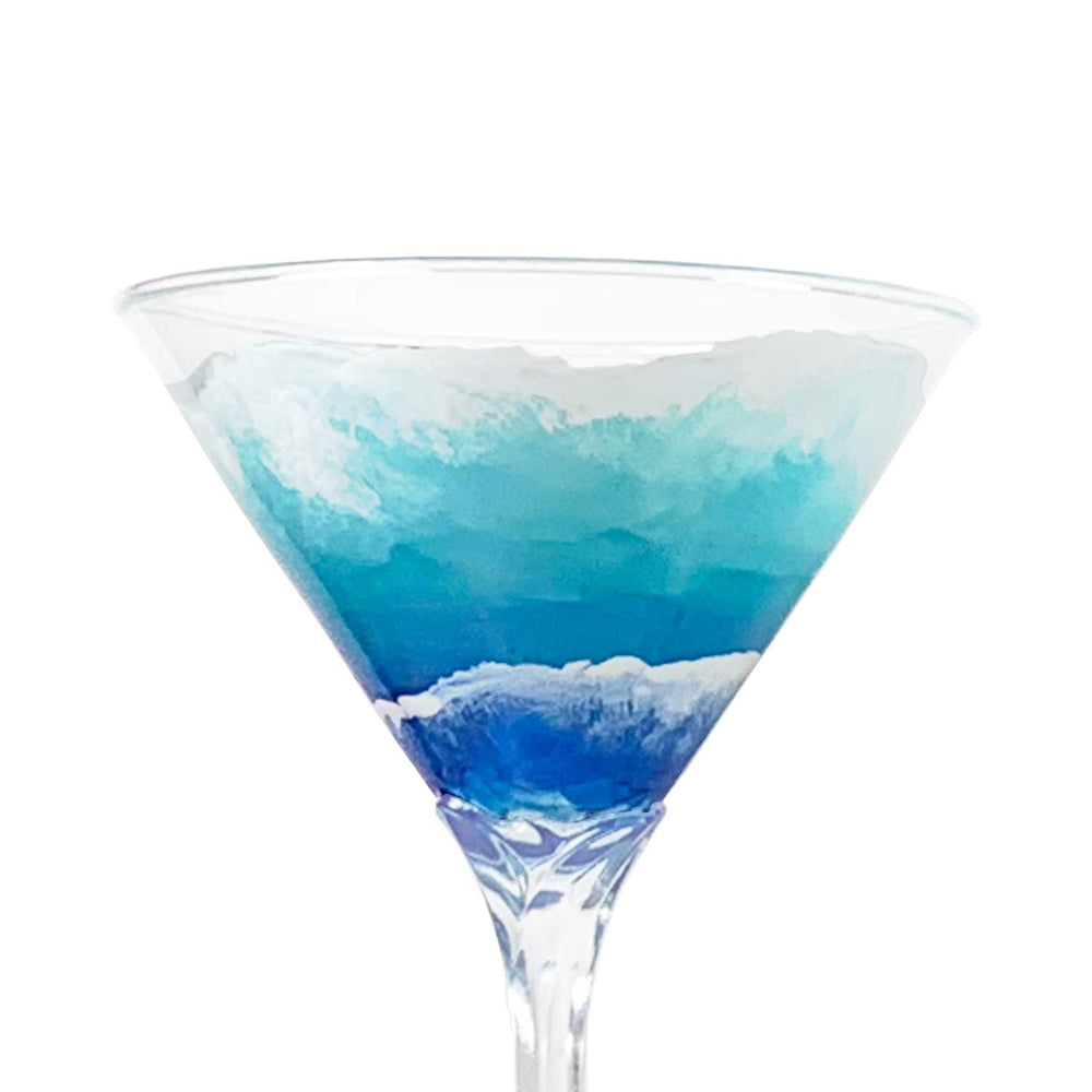 Close view of hand-painted martini glass with blue and white waves rolling up the beach. Luxury nautical barware.