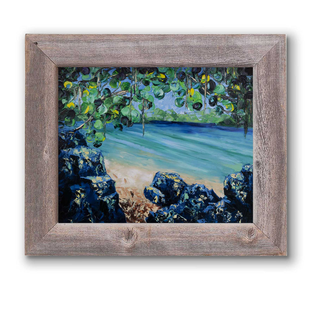 Framed beach house décor of tropical beach on a turquoise lagoon with lush green foliage