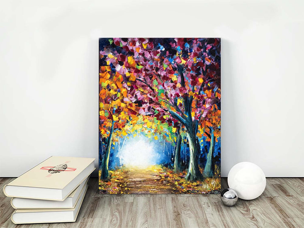 Colorful fall foliage lines a sunny forest path in an original oil painting on canvas. Shown as fall decor for living room.