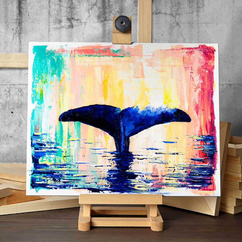 Original painting of deep blue whale tail against abstract rainbow background on easel