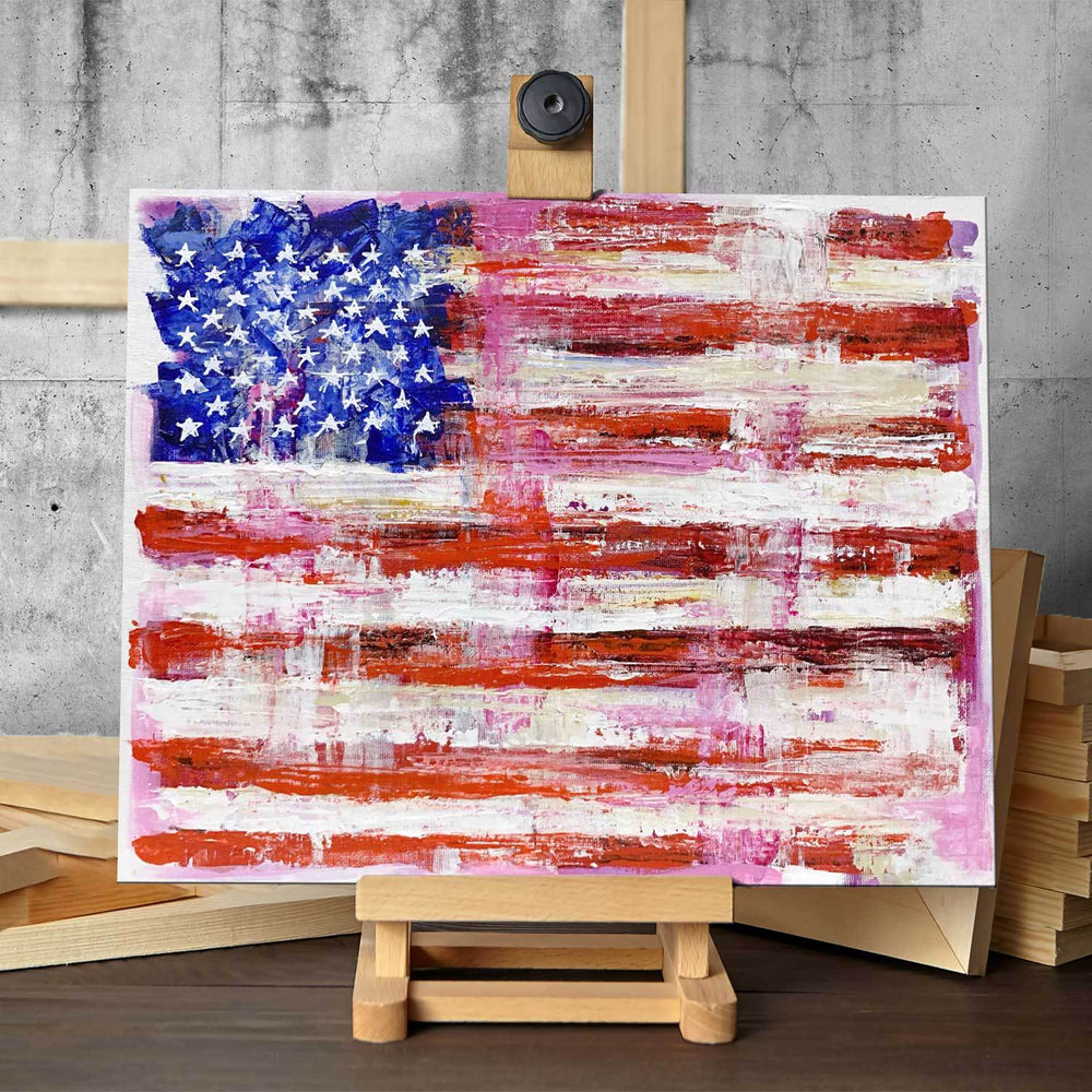 Original painting of American flag in rustic décor style, with pink highlights, sitting on a small artist's easel