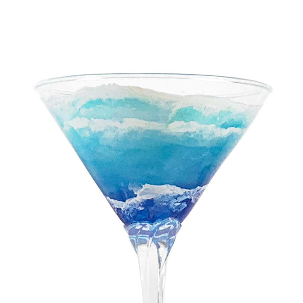 Close view of custom martini glass with hand-painted waves rolling up the shore. Beautiful coastal barware.