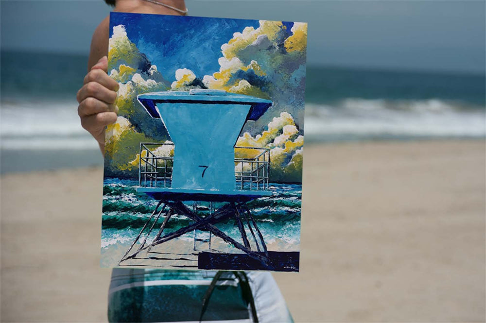 Surf Life painting of lifeguard tower on a beach landscape held by surfer