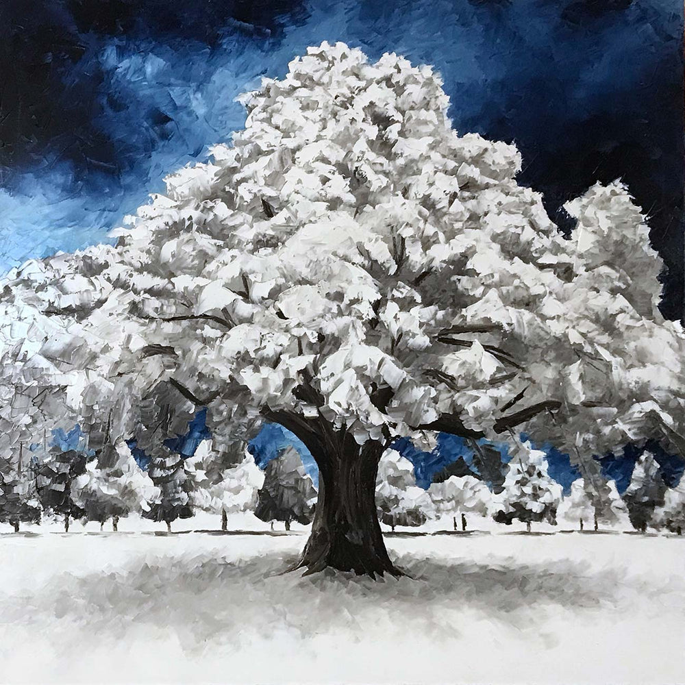 Nature wall art of snow covered winter tree against deep blue sky. Beautiful blue and white winter decor idea.