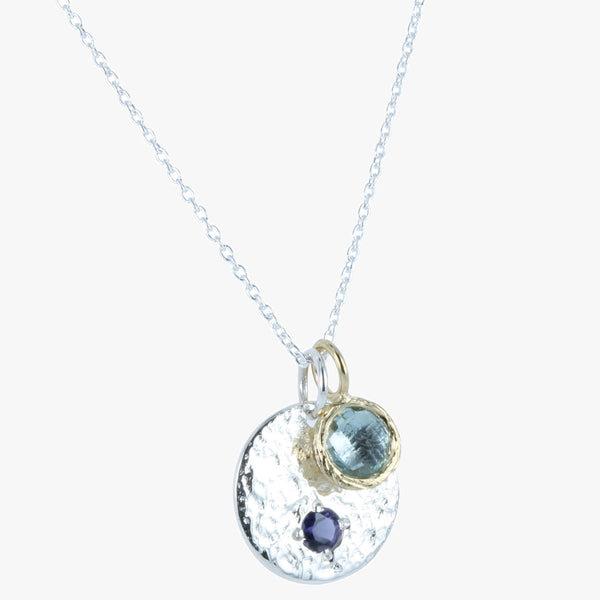 Sterling silver hammered disc with amethyst stone set in it and blue topaz charm set in gold vermeil bezel, on a silver chain