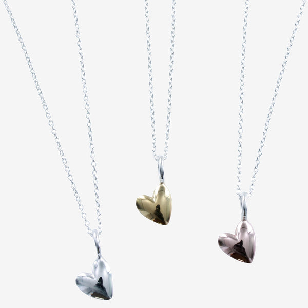 Sterling silver heart pendant available in silver, yellow and rose gold finish, hanging on a silver chain
