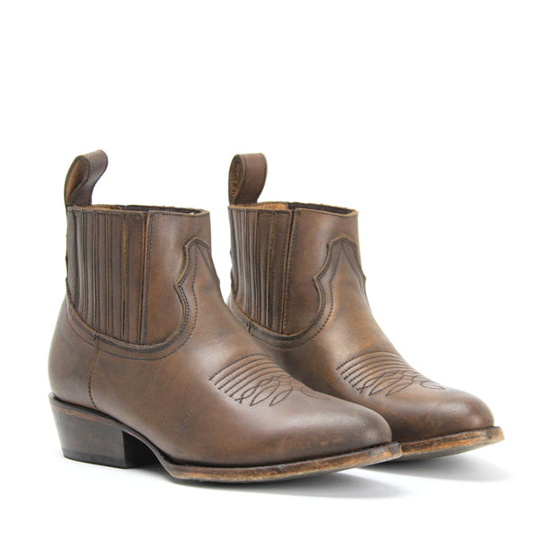MATISSE MUSTANG SADDLE WESTERN ANKLE BOOT. Sleek Pointed Toe. Heritage Stitch Detail. Saddle Tan Leather Upper. Handmade In Mexico.