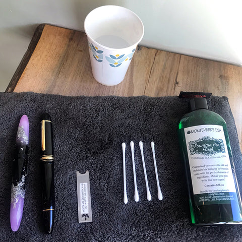 pens to be cleaned, nib removal tool, Q-tips, small cup of water, fountain pen flush; optional: silver polish
