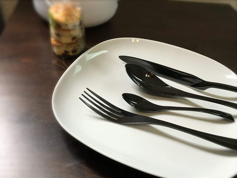 4 piece Jet Black Cutlery Set on a white plate