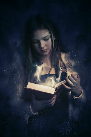 girl reading book with magic coming out of it