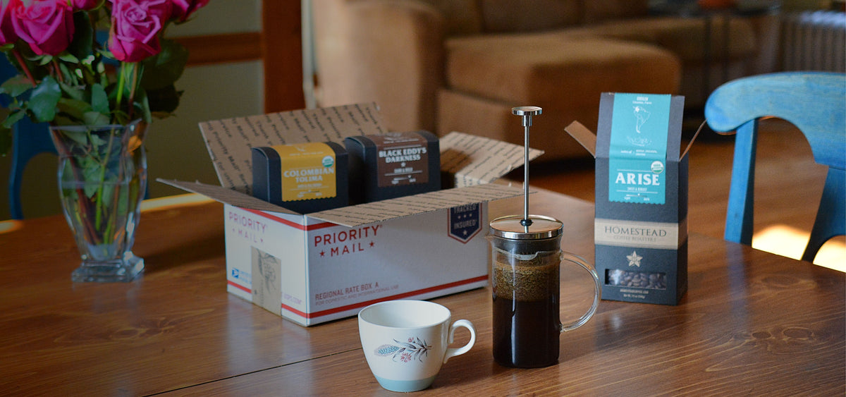 Organic coffee subscription box opened on dining table with french press