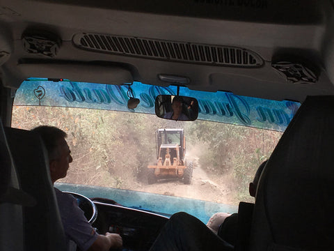 Looking out a jeep windshield at a tractor in Colombia