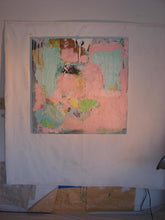 large square artwork on art studio wall pink green blue orange