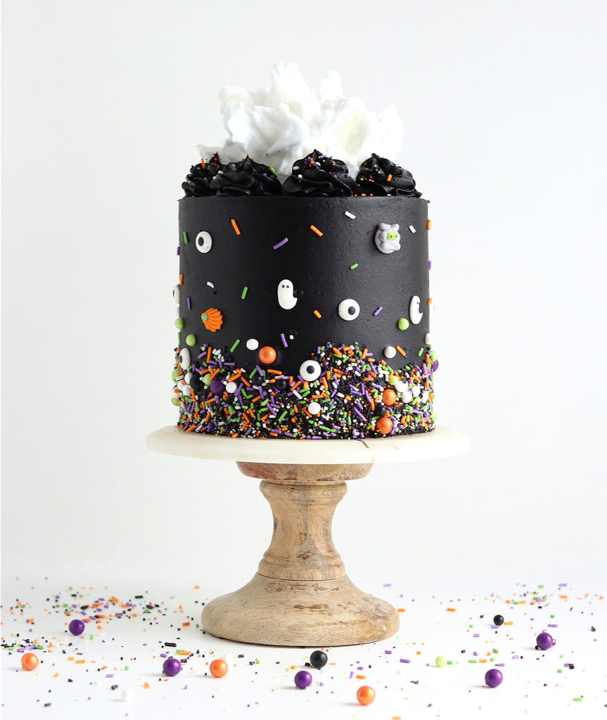 black Halloween cake with sprinkles by sugar and sparrow