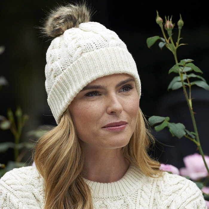 model of natural wool cable knit hat by west end knitwear