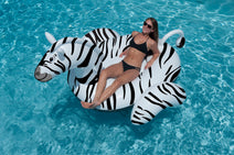 Woman relaxing on a Giant Ride-On Zebra Float