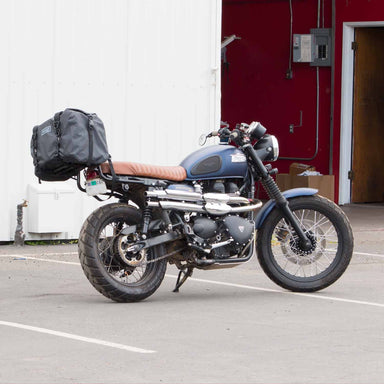 Blue Triumph Scrambler motorcycle with custom exhaust resting on it's kick stand with a waterproof duffle bag on the rear rack.