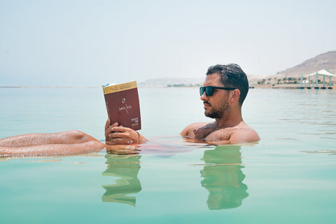 man reading while floating in water