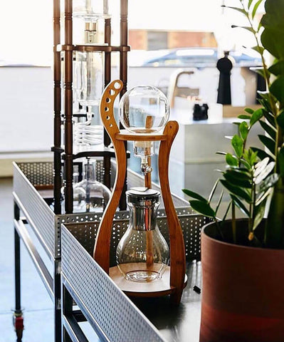 cold coffee drip beside a plant pot