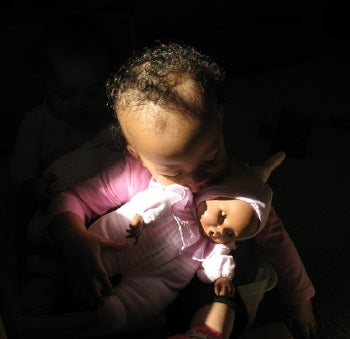 a Young black girl cuddling with her black baby doll