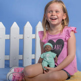 The Black Baby Tots Doll by Adora is a small doll here held by a model  for size comparison