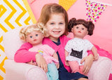 a young girl holding the blonde and brunette versions of the Cuddle & Coo dolls